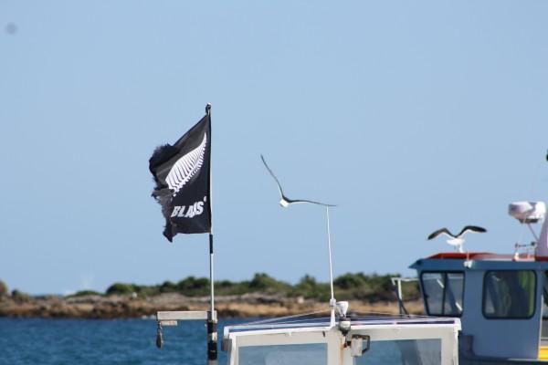 A fishing boat flying the All Blacks flag